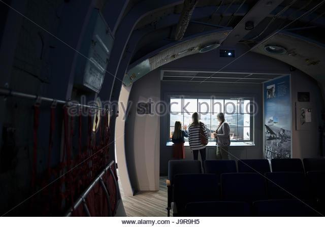 Docent explaining exhibit to mother and daughter in dark war museum - Stock-Bilder