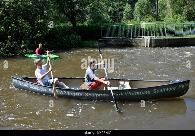 two teenage boys being instructed on canoeing by man in single seater kayak - Stock Image