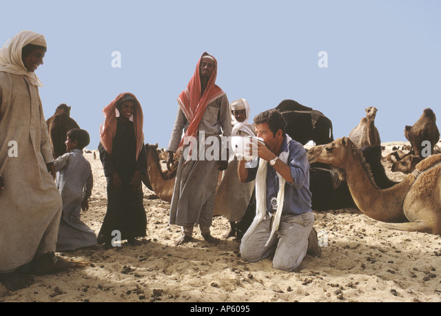 Saudi Arabia .Tor Eigeland drowns his thirst in a fresh bowl of camel's milk to the amusement of Al Murrah Bedu - Stock Image
