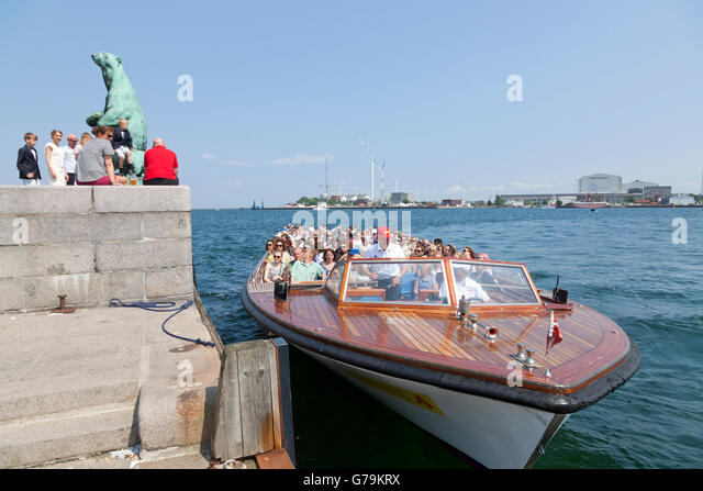 Visitors around the cast bronze sculpture 'Polar Bear with Cubs' and a canal cruise boat at the Langelinie - Stock Image