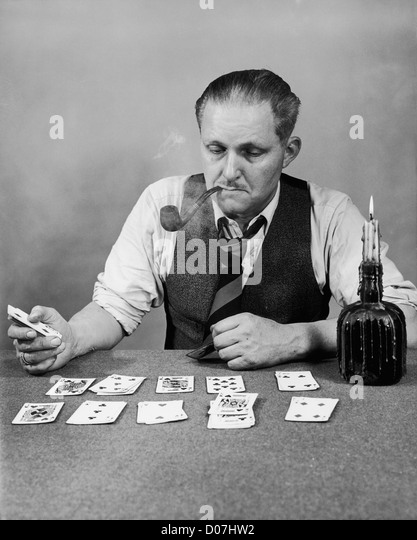 Man playing solitaire and smoking a pipe - Stock Image