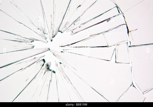 Impact point on a pane of glass - Stock Image