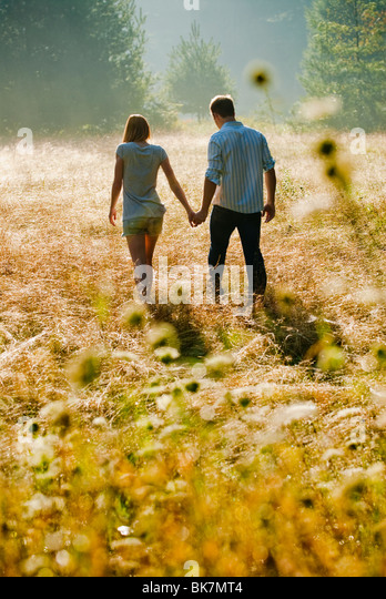Young couple walking through field holding hands - Stock Image
