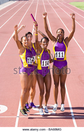 Team of female athletes cheering relay race victory - Stock Image