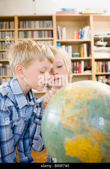 Brothers and terrestrial globe - Stock Image