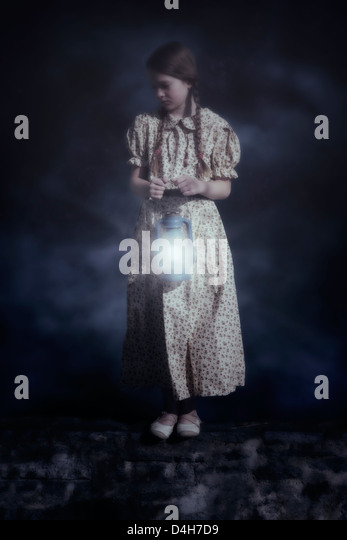 a girl with a lantern standing on a wall - Stock-Bilder