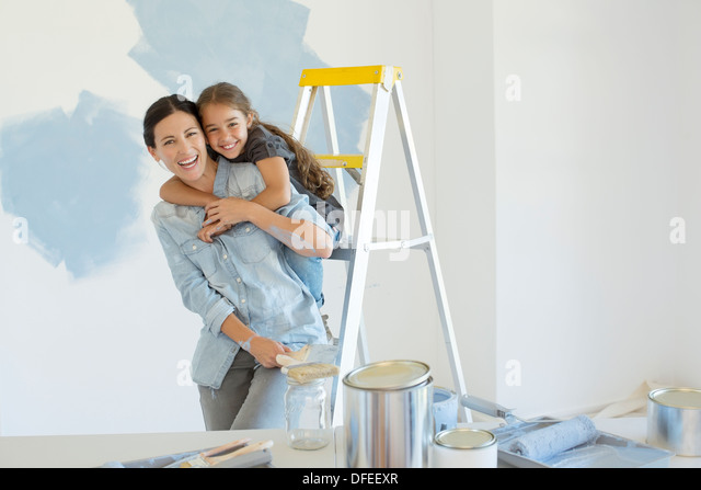 Portrait of mother and daughter hugging near paint supplies - Stock Image