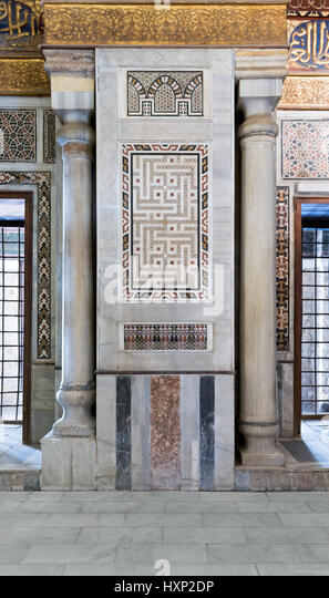 Architectural detail of an old historical decorative calligraphy mosaic colored panel between two marble columns, - Stock Image