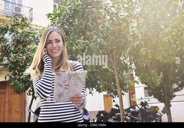 Young female tourist with map and cellphone, Valencia, Spain - Stock-Bilder