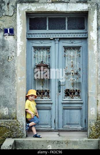 Portrait of a cute little kid leaning on a retro door - Stock Image