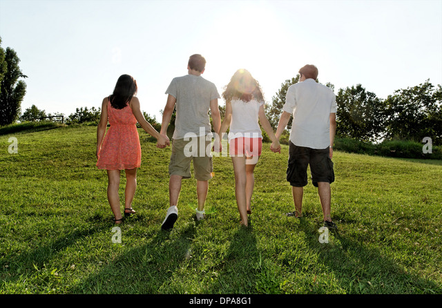 Group of young adults walking and holding hands - Stock-Bilder