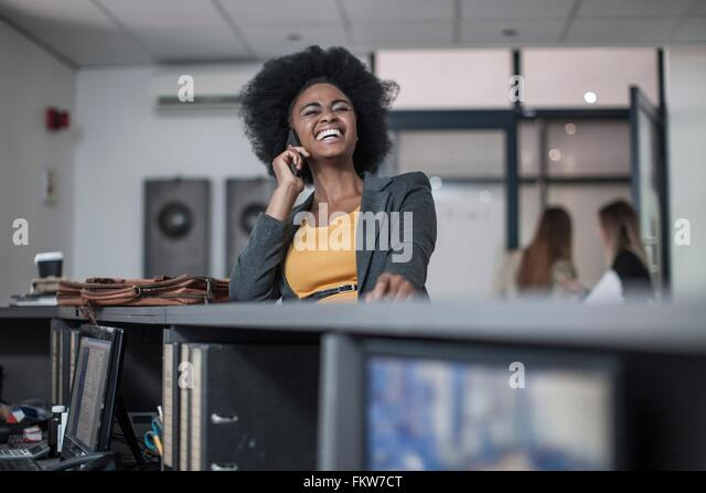 Young businesswoman chatting and laughing on at office reception - Stock Image