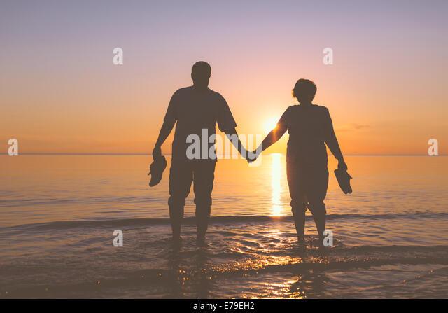 Happy senior couple silhouettes on the beach - Stock-Bilder