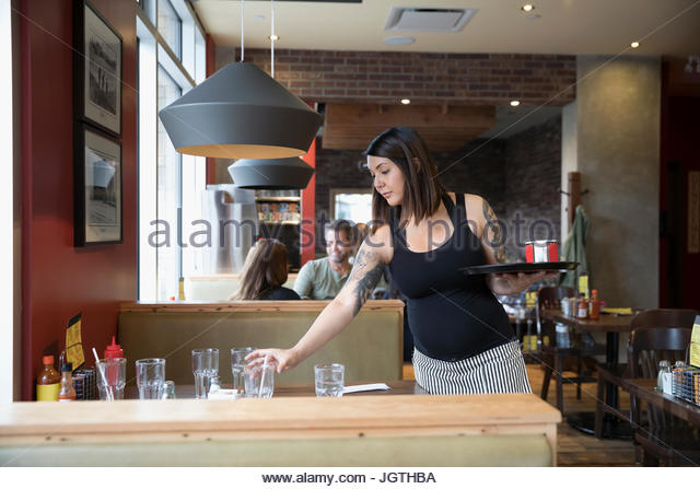 Pregnant waitress bussing table in restaurant - Stock Image