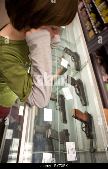Eight year old child looking at hand guns in a display case, southwestern United States. - Stock Image