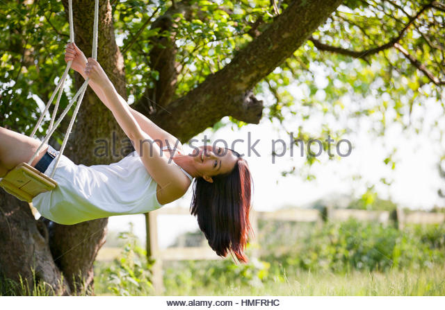 Portrait happy woman swinging on tree swing in sunny summer rural yard, carefree, fun - Stock-Bilder