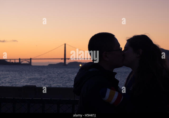 A young couple kiss at sunset in front of the Golden Gate Bridge in San Francisco, California. - Stock Image