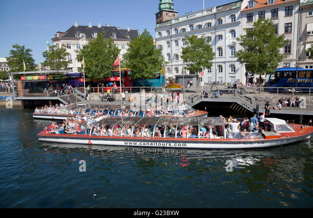 A busy day for the canal tour boats at the Gammel Strand place of call close to the Christiansborg Palace. - Stock Image