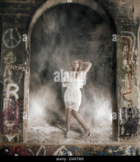 Woman between columns standing in dust cloud - Stock Image