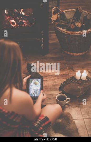 Woman sitting in front of a wood burning stove holding a digital tablet - Stock Image