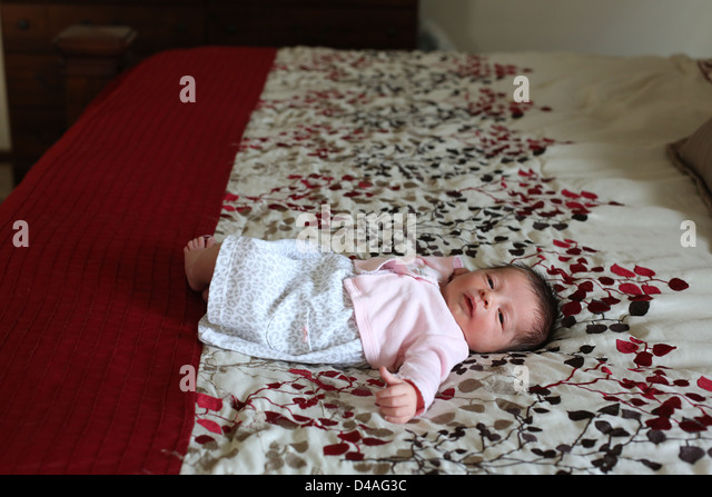 A tiny newborn baby lying on a large bed. - Stock Image