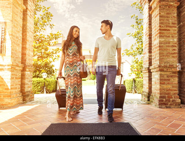 Young couple standing at hotel corridor upon arrival, looking for room, holding suitcases - Stock-Bilder