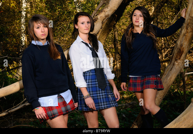 Three high school teenage girls in private school uniforms hanging out in a thick forest Toronto - Stock Image
