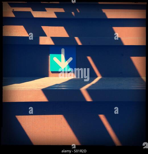 Arrow sign on stairs - Stock Image