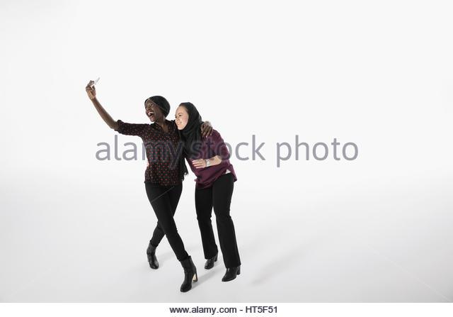 Playful women friends taking selfie with smart phone against white background - Stock-Bilder