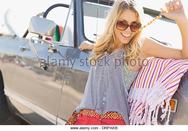 Portrait of woman leaning against off-road vehicle eating candy - Stock Image