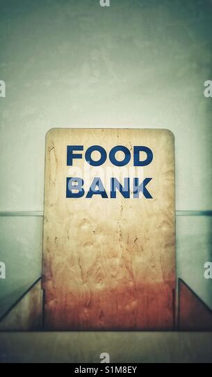 Empty food bank collection bin against a blank wall, North America. - Stock Image