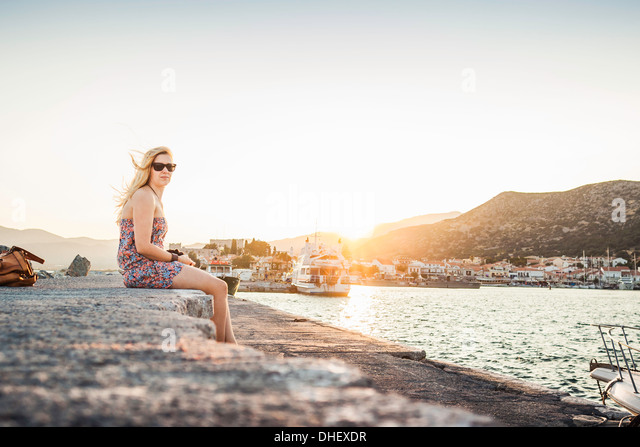 Woman sitting at coast at Pythagoreio, Samos, Greece - Stock Image