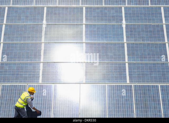 Worker examining solar panels - Stock Image