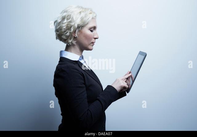Studio portrait of blond businesswoman looking at digital tablet - Stock-Bilder