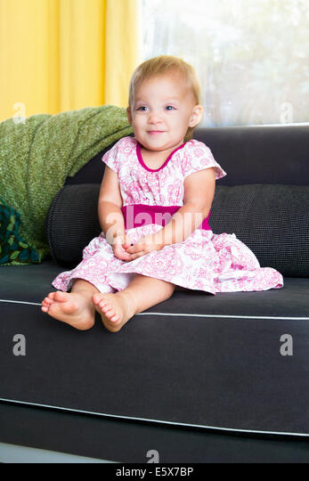 Portrait of shy baby girl sitting on sofa - Stock Image