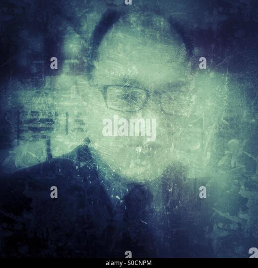 Bald man in his 50s wearing business suit and squarish eyeglasses, with grunge texture overlay. - Stock Image