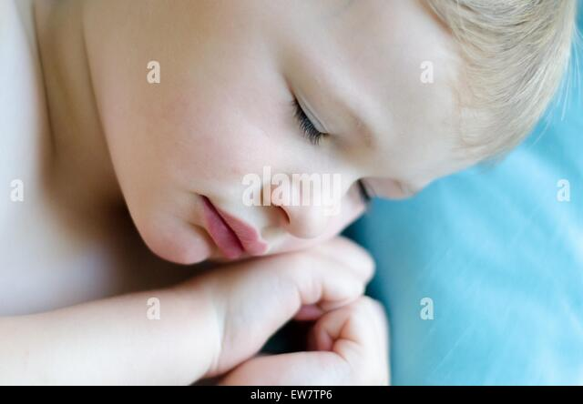 Close-up of a boy Sleeping With hands in a heart shape - Stock Image