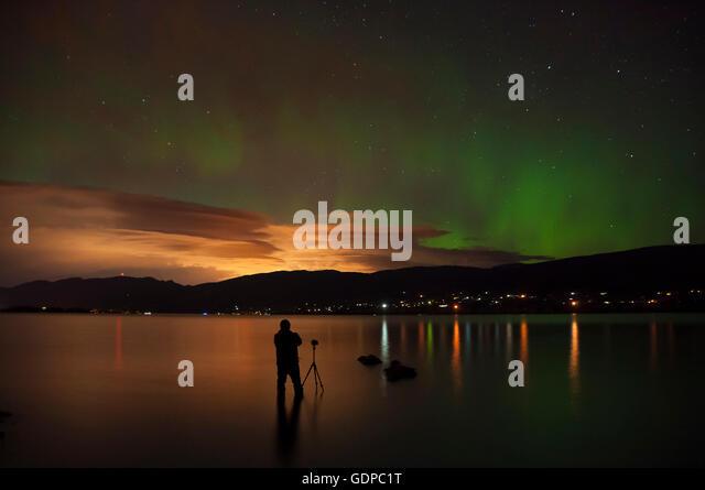 Photographer in Okanagan Lake photographing aurora borealis, Kickininee Provincial Park, Penticton, British Columbia, - Stock Image