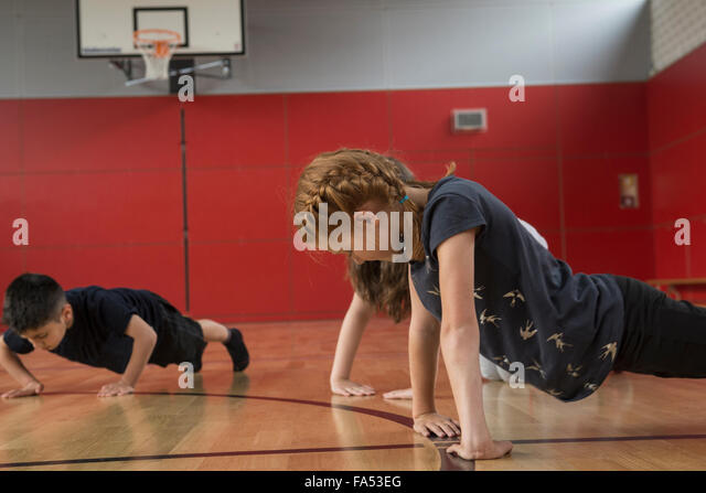 Children doing press-ups in sports hall, Munich, Bavaria, Germany - Stock Image