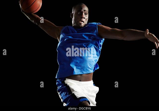 Male basketball player shooting ball - Stock Image
