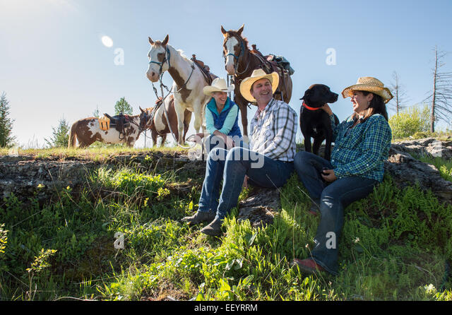 Stacia McAdams (in blue vest) Mike McAdams and Alicia Hammond ride at Artemis Acres Guest Ranch in Kalispell, Montana - Stock Image