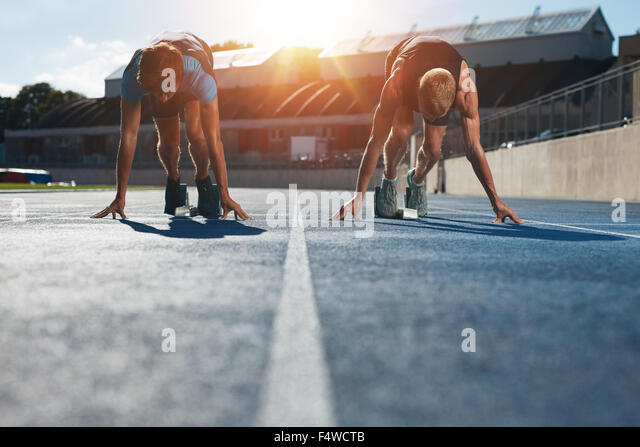 Sprinters at starting blocks ready for race . Athletes at starting position on athletics stadium race track with - Stock Image