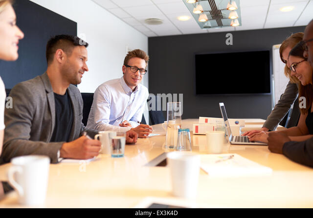 White male executive smiling at camera during a meeting with colleagues - Stock Image