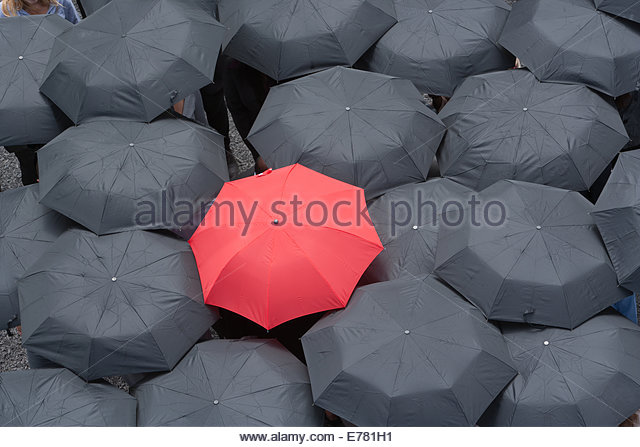 One red umbrella at center of multiple black umbrellas - Stock Image