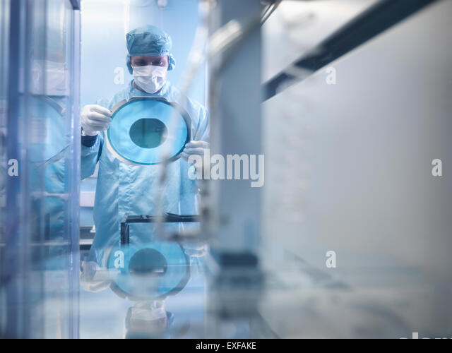 Electronics worker holding silicon wafer by cutting machine in clean room - Stock Image