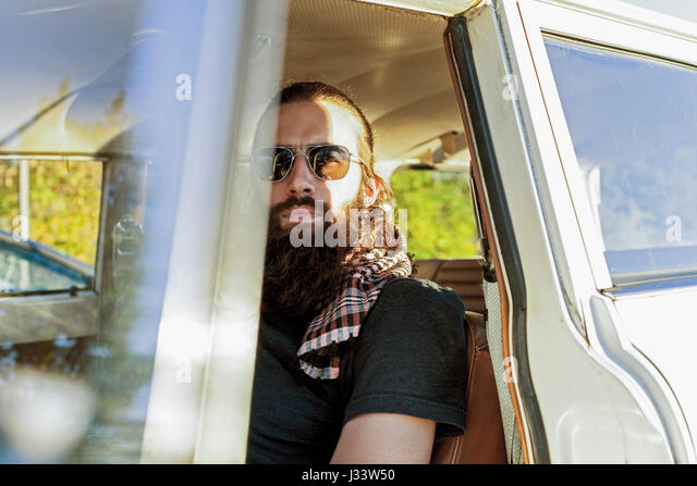 Handsome young man sitting in a car - Stock Image