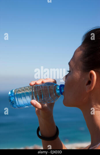 Woman Drinking Water from Bottle by Ocean - Stock Image