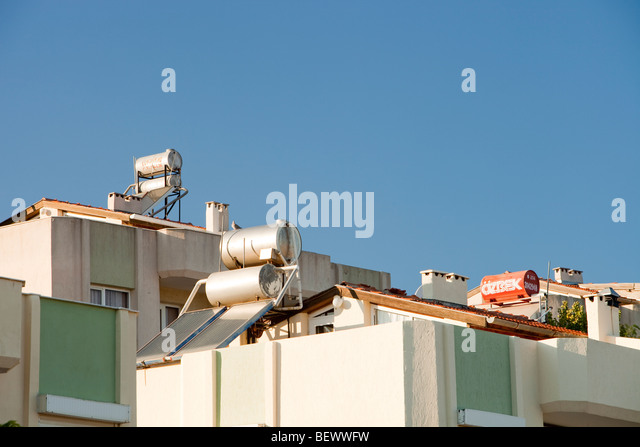 Solar water heaters on house roofs in Teos, Turkey. - Stock Image