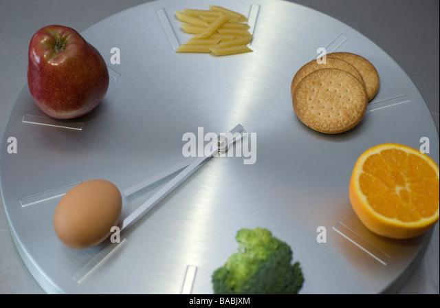 clock food control- pasta, biscuits, orange, apple, egg and broccoli - Stock Image