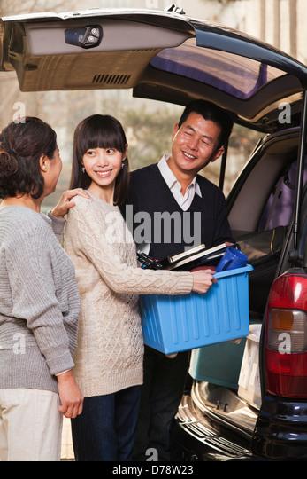 Family unpacking minivan for college, Beijing - Stock Image